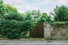 Front View Of Wooden Garden Gate In Stone Wall