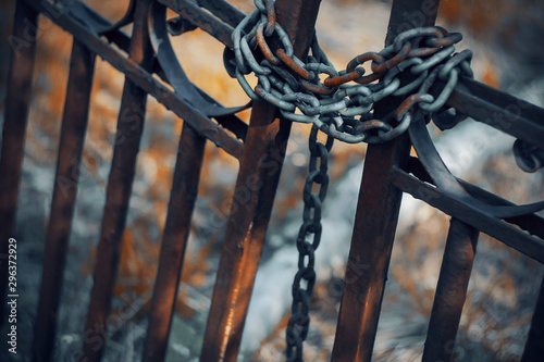 Gloomy rusty metal fence, which is closed on a metal long chain. Behind the fence is red grass and a path to the mystical land.