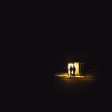 Man And Woman Walking By Bus Stop At Night