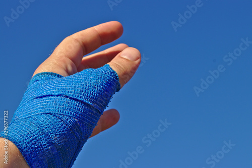 Wallpaper Mural left male hand with a blue elastic bandage
