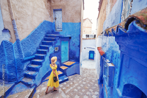 Staande foto Marokko Colorful traveling by Morocco. Young woman in yellow dress walking in medina of blue city Chefchaouen.