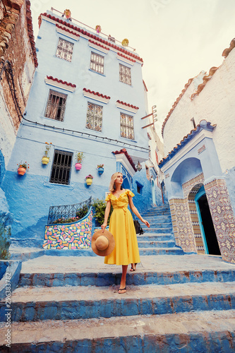 Papiers peints Maroc Colorful traveling by Morocco. Young woman in yellow dress walking in medina of blue city Chefchaouen.