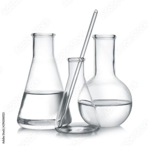 Fotografía  Laboratory glassware with liquid samples on white background