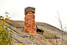 Old Collapsing Chimney On A Red Brick Roof