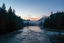 Scenic View Of River Passing Through Mountains During Sunset