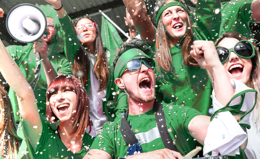 Fototapety, obrazy: Young amateur football fan supporters cheering with confetti watching local soccer cup match at stadium - Friends people group on green t shirts having excited fun on sport world championship final