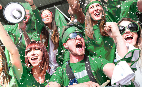 Young amateur football fan supporters cheering with confetti watching local socc Canvas Print