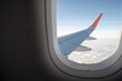 View from inside airplane window. Looking outside at the airplane wing seeing clouds and a blue sky.