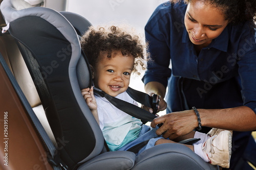 Fotografiet  Side view of a happy little boy looking at camera while his mother buckling him