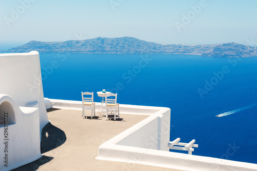 Foto auf Gartenposter Santorini Two chairs on the terrace with sea view. White architecture on Santorini island, Greece. Travel destinations concept