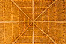 Close - Up Of The Interior Of The Thatched Roof With A Crossbar. Use For Backgrounds Or Textures With Copy Space. Thatched Roof Inside In The Form Of Cobwebs . Sunny Weather Under The Roof. Real Straw