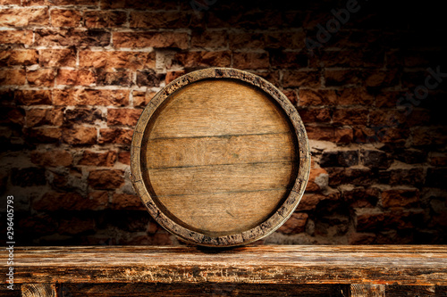 Foto Old wooden wine barrelwith table board and brick wall background.