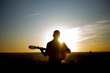 Young Boy Playing Guitar In The City Of Madrid, Spain In The Background.