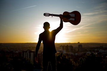 Young boy picks up the guitar in the city of Madrid, Spain in the background.