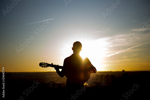 Young boy playing guitar in the city of Madrid, Spain in the background. - 296407114