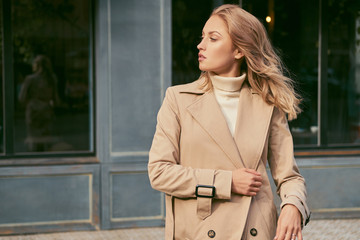 Side view of attractive girl in trench coat confidently looking away on street
