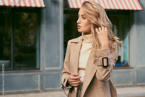 Fotomural  Side view of beautiful pensive blond girl in trench coat thoughtfully looking aw