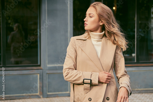 Carta da parati Side view of attractive girl in trench coat confidently looking away on street