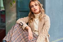 Beautiful Blond Girl In Stylish Trench Coat And Skirt Confidently Looking In Camera Outdoor
