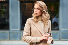 Beautiful Blond Girl In Stylish Trench Coat Thoughtfully Looking Aside On Street