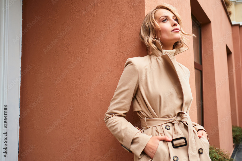 Fototapeta Beautiful stylish blond girl in trench coat dreamily looking away outdoor