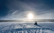 One Person Drives Snowmobile In Very Cold Mountains In Sweden, Frosty Fog Around Bright Sun Creates Halo Effect, Wild Birches Forest And Mountains Behind Driver. Hemavan -Tarnaby Area In Lappland