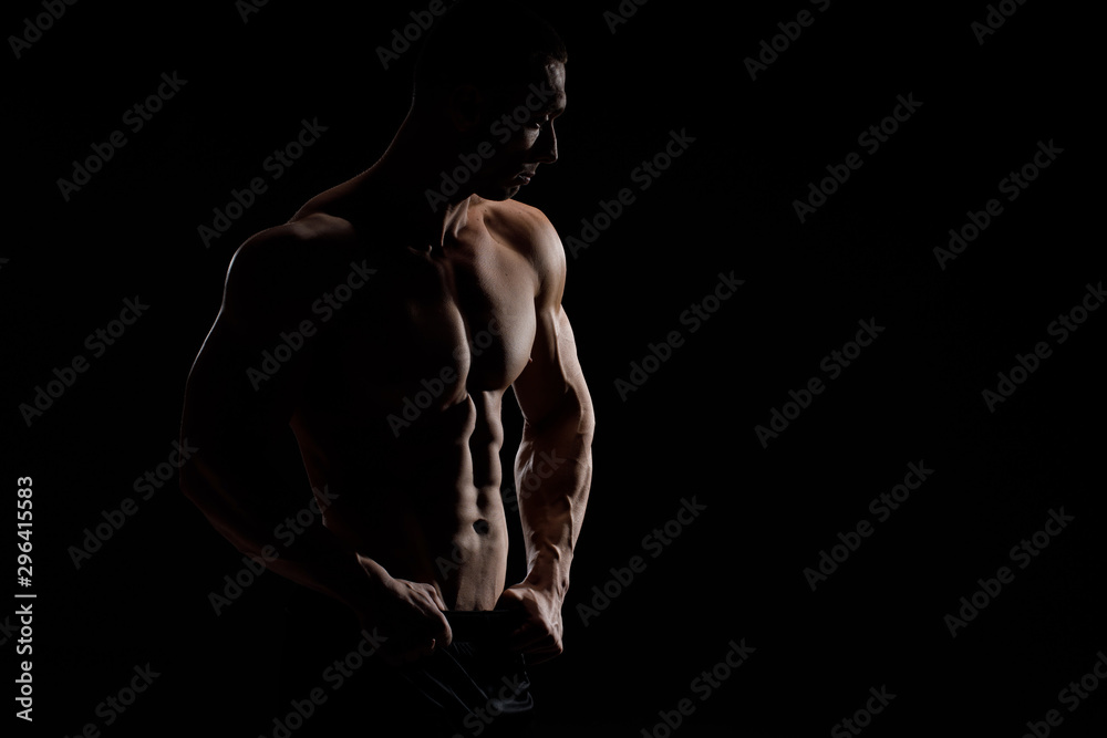 Fototapety, obrazy: Muscular model sports young man in jeans showing his press on a black background. Fashion portrait of sporty healthy strong muscle guy. Sexy torso.