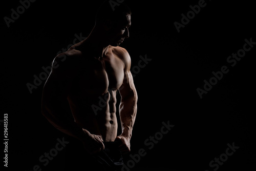 Muscular model sports young man in jeans showing his press on a black background Fototapet