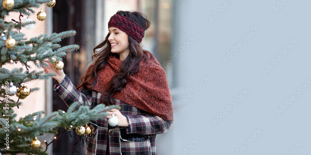 Fototapety, obrazy: Beautiful joyful woman portrait in a city. Smiling  girl wearing warm clothes and hat  in winter. Christmas time with natural decorative fir tree. Copy space