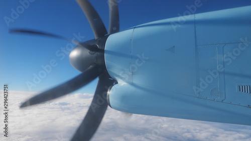 Fotografia, Obraz  Detail of spinning propeller on plane wing, flying over white fluffy sky on sky