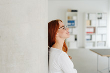 Young Woman Standing Daydreaming In The Office