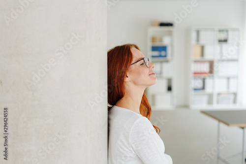 Leinwand Poster Young woman standing daydreaming in the office