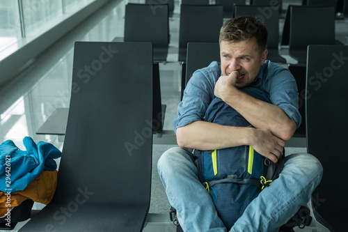 Fotomural  Young man at the airport waiting for his plane looking at the windoe