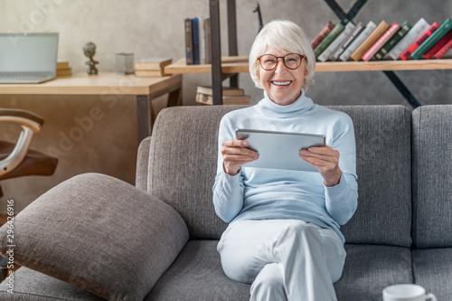 Portrait of smiling mature woman using digital tablet on sofa at home Wallpaper Mural