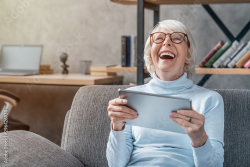 Obraz Happy senior woman looking and laughing at her digital tablet on sofa - fototapety do salonu
