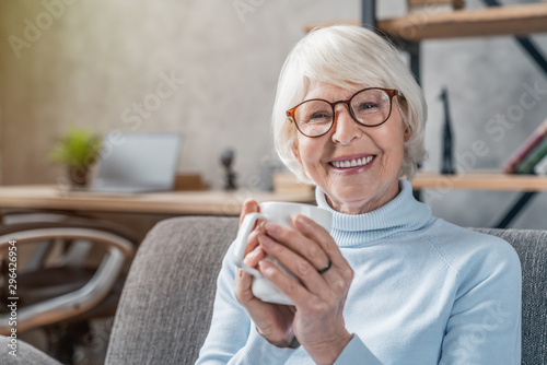 Fotografia Senior woman drinking hot drink sitting on sofa at home