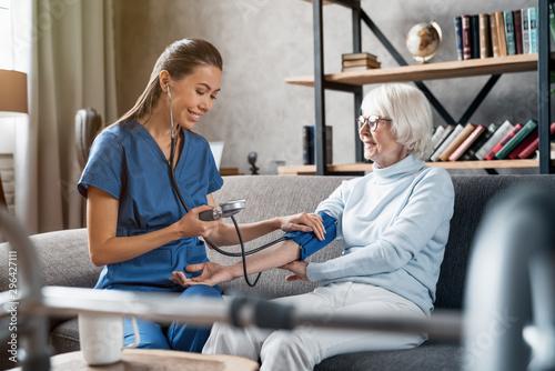 Carta da parati Nurse measuring blood pressure of elderly woman indoors