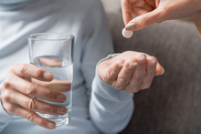 Caring Nurse Giving Pills To Senior Woman With Glass Of Water In Hand