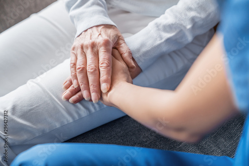 Close up image of caregiver holding hands of elderly patient during home visit Tapéta, Fotótapéta