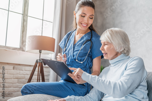 Valokuvatapetti Smiling senior woman reading medical tests results in hands of nurse visiting he