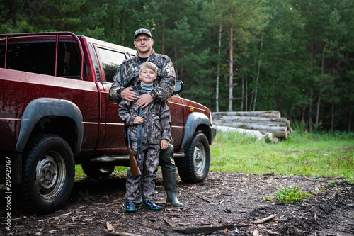 Cadres-photo bureau Chasse Happy hunter with his son near their pickup truck before hunting in a forest