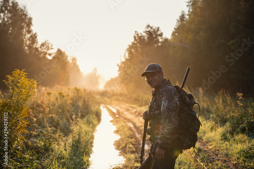 Poster Chasse Bird Hunter at Sunrise going for hunt in a forest with his shotgun rifle.