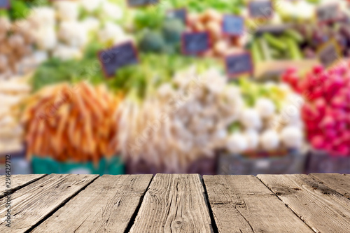 Blurred fresh vegetables at market with empty rustic wooden planks on the foreground. Can be used for advertise products. Mockup image. - 296429712