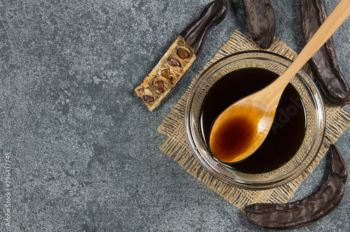 Obraz na plátně carob molasses in glass bowl and in wooden spoon and carob pods on rustic backgr