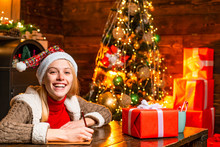 Beautiful Woman In Santa Hat Helper With Christmas Gift In A Red Box. Rituals For The New Year. Christmas And Happiness Concept.