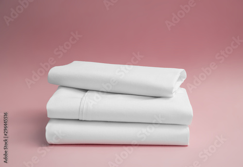 Stack of white bedding against pink backdrop, folded soft bed clothes, stack of Fototapeta