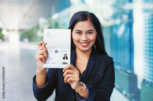 Photo Asian woman showing valid visa and work permit in her passport
