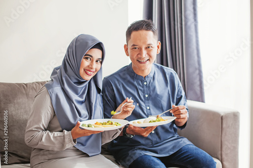 Beautiful muslim southeast asian couple eating together, looking at camera Canvas Print
