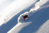 Extreme snowboarder has fun riding fresh powder snow off piste in white mountains. Pro rider snowboarding and carving freshly fallen snow in mountain wilderness. winter extreme sports background