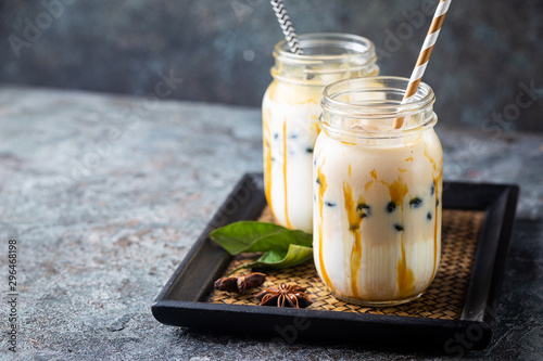 Light brown creamy bubble tea with milk and black tapioca in a glass jar on gray background